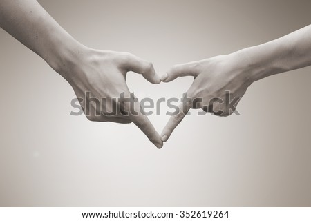 close up focus on couple man and woman hands make heart shape over blurred beige sepia color vintage tone background.