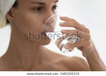 Close up focus on female hand hold glass of mineral aqua. woman drinks clear water reduces thirst. Healthy everyday life habit, caring about beauty of skin and whole body, healthcare treatment concept