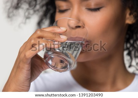 Close up focus on female hand holding glass african woman drinking still water having thirst healthy lifestyle body skin care hydration aqua balance regulation concept, studio shot on grey background