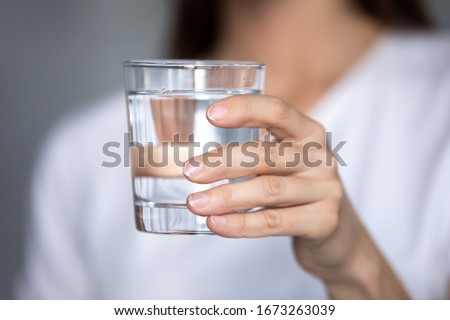 Close up focus on glass of pure distilled water in female hands. Young thirsty woman holding clear liquid aqua, ready drink, prevent organism from dehydration, body balance, healthcare, refreshment.