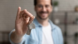 Close up focus on keys with keychain in the form of house in male hands, happy young man homeowner purchased new apartment, feeling excited of moving in new flat, tenancy accommodation concept.