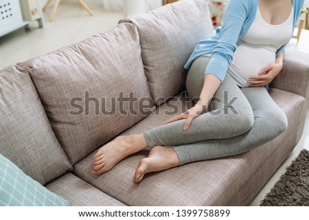 close up focus on legs cramps during pregnancy. Pregnant unrecognized woman gets feet hurting painful resting at home on couch sofa. asian lady in casual wear future mom massage feet baby in belly