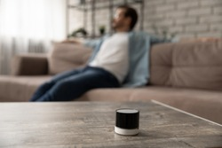 Close up focus on mini smart wireless loudspeaker on table in living room, man in background listen to good quality sound music on mobile speaker audio device or gadget, new technology concept