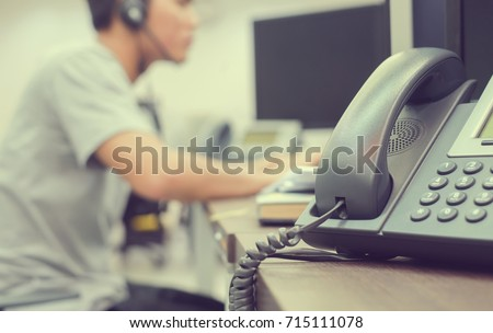 close up focus on telephone with blurred of call center employee man working in operation room for contact with customer or partner,technology and business concept