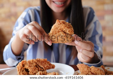 close up focus woman hand hold fried chicken for eat,girl with fast food concept #659161606
