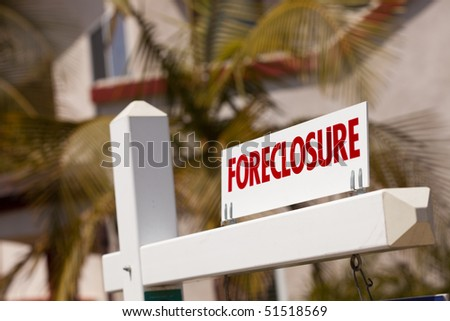 Close-up Foreclosure Real Estate Sign in Front of House. stock photo