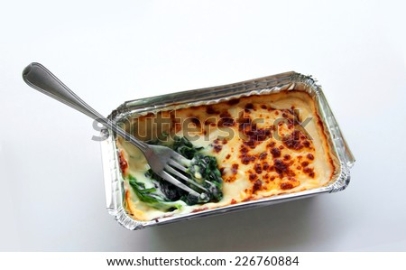 close up fork baked spinach with cheese in silver package on isolate
