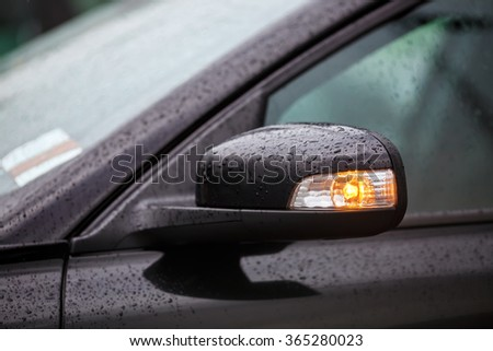 Close-up fragment black car with rain drops. Modern car side mirrors with turn signal. Shallow depth of field. Selective focus. #365280023
