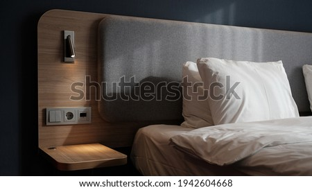 Close-up fragment of bedroom with empty bedside table, reading lamp and a USB socket in modern interior design home or hotel. Soft pillow and blanket, stylish comfortable furniture. Sun shadows.