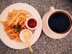 close up frenchfries serve with tomato sauce and mayonaise as well as a cup of coffe complete the lunch break