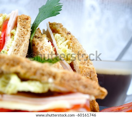 close up fresh and delicious classic club sandwich over a black glass dish with coffee and vegetable