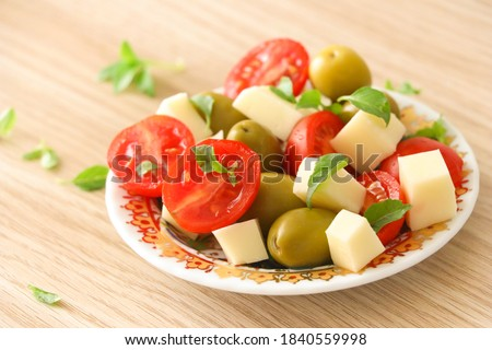 Close up fresh and healthy snack or breakfast which includes organic cherry tomatoes, green olives, cheddar cheese cubes and freshly picked basil leaves. (Served on a wooden kitchen table)  Photo stock ©