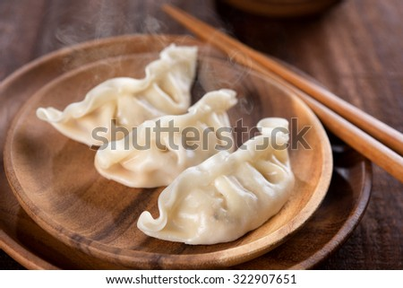 Close up fresh boiled dumplings with hot steams on wood plate. Chinese food on rustic old vintage wooden background.