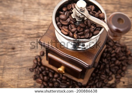 Close up fresh coffee bean in coffee bean grinder next to coffee bean on wooden table top