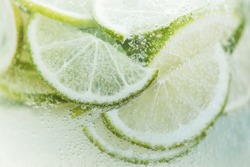Close-up fresh lemon slices in cold lemonade with bubbles. Summer tropical beverage