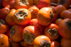 close up Fresh ripe persimmons placed on table in market. Organic persimmon fruit in pile at local farmers market. Persimmons background.