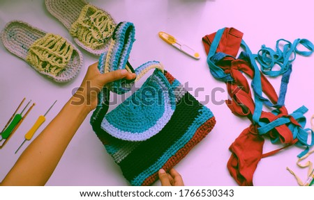 Close up from top view woman hand hold colorful handmade bag from recycle old t shirt on white background, reuse clothes by cut in yarns then crochet to make diy product in leisure activity Foto stock ©