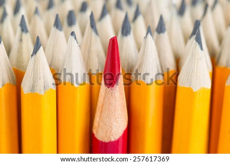 Close up front image of stacked pencils with focus on tip of red pencil in middle of the stack