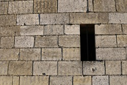 Close up front outdoor view of part of a beige white stone wall with a small opening, northern France. Abstract design with pattern of rectangular blocks and lines. Ancient masonry facade.