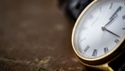 Close up front view of a modern wrist watch on the table. Soft focus. Free space for text