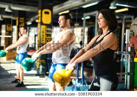 Close up front view of focused and motivated strong young fitness couple in sportswear doing exercizes crouching with the kettlebells reversed and doing squats in the gym at sunny day #1081903334