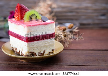Shutterstock Close-up fruit cake with  white cream on wooden table have space to write.