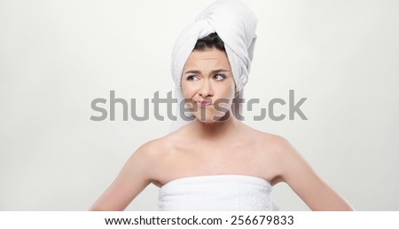 Close up Frustrated Fresh Young Woman Wrapped her Body and Hair with Bath Towel. Isolated on White Background.