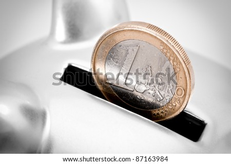 Close-up full frame image of one Euro coin partially inserted into the slot of a silver piggy bank.