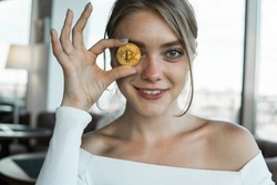 Close up fun emotional young female is holding bitcoin in front eye. Online virtual future currency concept. Beauty woman head with Bitcoin money in eye. Digital cryptocurrency bitcoin.