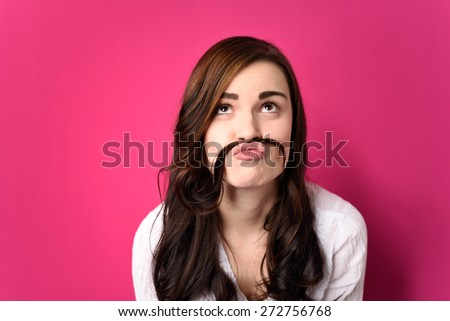 Close up Funny Young Woman Putting her Hair Between Nose and Lip and Looking Up. Isolated on a Pink Background.
