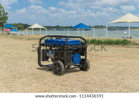 Close-up gasoline powered portable generator on lakeshore sunny day Texas, US. Blurry high peak frame tent in background. Outdoor equipment standby, mobile backup for disaster recovery or construction #1114436591