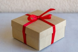 Close-up gift cardboard box with a red bow. The concept of gifts, festive mood, home comfort.