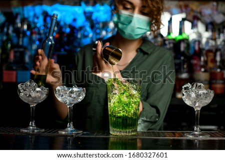 Close-up girl bartender in medical mask carefully pours green liquid into glass with ice using beaker. Medical mask for prophylaxis and protection from coronavirus COVID-19.