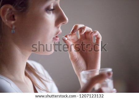 Close up girl hold glass still water and pill. Sick woman taking putting pill in mouth painkiller or antibiotic medicine, depression treatment chronic disease or biologically active supplement concept