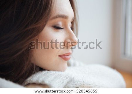 Close up girl in sweater near the window. eyes closed. #520345855