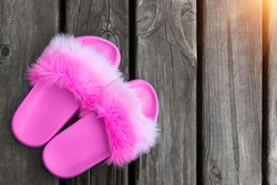 Close-up girl or woman empty glamour fashion fluffy fuzzy slippers standing on wooden floor board background. flip-flop sliders near poolside. Vacation and travel concept. Toned. Copyspace