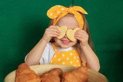 Close up glad joyful laughing child closing eyes by two cookies pastry in shape of heart in her hands, indulges. Little girl in yellow apron posing on green background. Concept Easter holliday baking