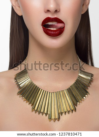 Close up glamorous image of a female predator with licking red lips. On the neck of the girl gold jewelry and sparkles on the body. Beautiful transparent skin. Spa care or beauty care. Beauty sexy