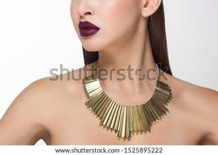 Close up glamorous image of a female with a bite of purple lips. On the neck are golden jewels and sparkles on the body. Beautiful transparent skin. Spa care or beauty care. Beauty sexy woman