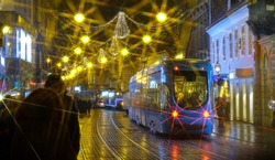 CLOSE UP: Glaring Christmas lights illuminate the picturesque festive city streets at night. Blue trams move through the busy shopping street in downtown Zagreb on a cold winter night in December.