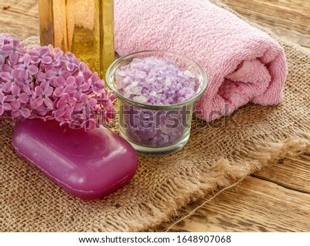 Close-up glass bowl with sea salt, soap, bottle of oil, lilac flowers and towel for bathroom procedures on sackcloth and wooden boards. Spa products and accessories. Top view.