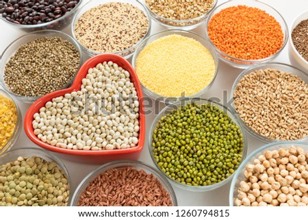 Close-up glass bowls with cereals, beans and seeds with red heart-shaped bowl in the middle on white background. #1260794815