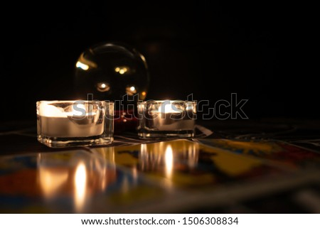 Close up glass candle holder.Burning candles between crystal ball and  facing up tarot cards.Tarot reader or Fortune teller reading tarot cards and forecasting concept.Mystic and darkness background.