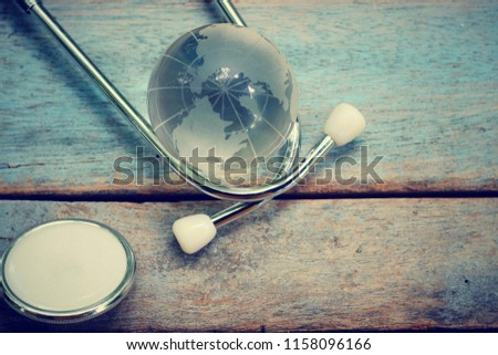 close up glass global and stethoscope on old wood table, world health day, medical and healthcare technology concept, vintage tone #1158096166