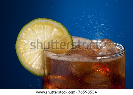 Close-up glass of cola with lime and ice on blue background