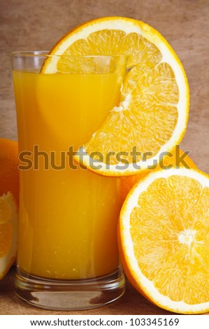 close up glass of fresh orange juice with slice of orange on a vintage wooden background