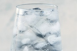 close up glass with ice water and ice cubes on white textured background. A refreshing and chilling drink in hot weather. soft focus