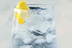 close up glass with ice water and lemon, ice cubes on white textured background. A refreshing and chilling drink in hot weather. Minimalist style. soft focus