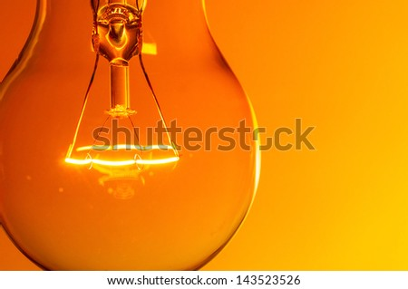 Close up glowing light bulb on orange background