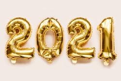 Close-Up gold foil balloons numeral 2021 on beige background. Merry Christmas and happy new year concept.